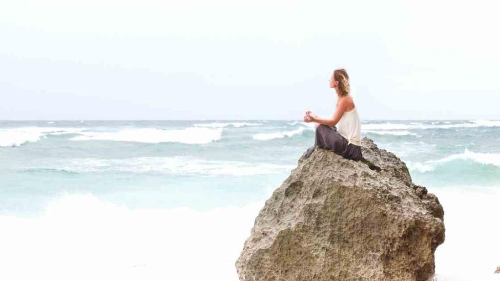 Frau auf Felsen am Meer, meditiert, sieht in die Wellen