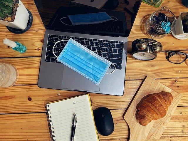 Schreibtisch, Sicht von oben, Utensilien, Laptop mit Maske auf Tastatur