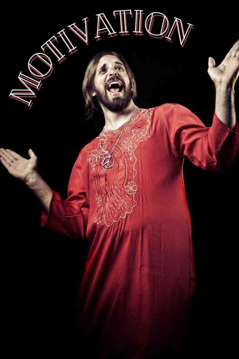 Motivation Mann mit roten langem Gewand strahlt, Mund gehöffnet, Hände präsentieren Wort