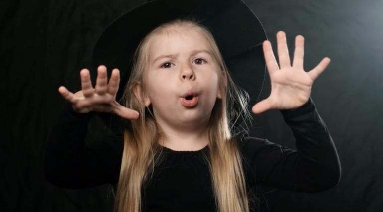 Kind mit dunkler Kleidung, Zauberhut, spricht Zauberformel