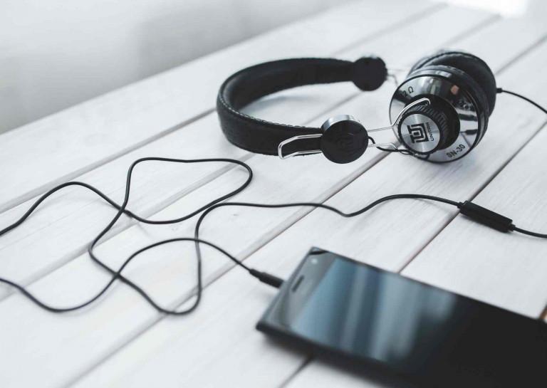 Generationen: Draufsicht auf Schreibtisch, Handy mit eingesteckten Köpfhörer, soll digitales Lernen ausdrücken