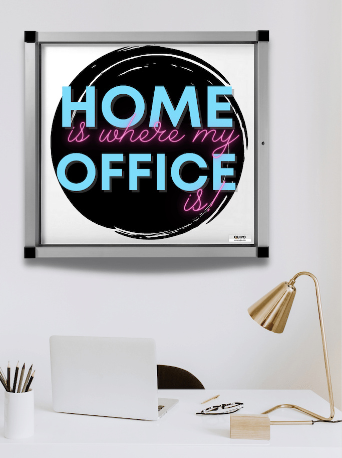 Homeoffice Schreibtisch mit Schaukasten Spruch in hellblau und pink, Hintergrund schwarzer Kreis, helle Umgebung, Laptop auf dem Tisch