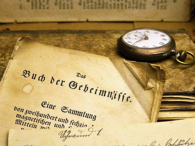 """Altes vergilbtes Buch Schrift """"Buch der Geheimnisse"""" ist zu lesen, Taschenuhr liegt daneben"""