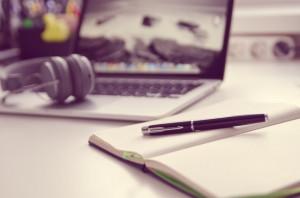 Büroumgebung, Schreibtisch mit Laptop und Kopfhörern, im Vordergrund ein Notizbuch mit Füller