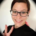 Frau mit dunkler Brille und dunklen Haaren, grinst, zeigt Viktory-Zeichen
