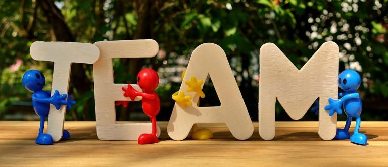 Holzletter bilden Wort TEAM, bunte Figuren stehen drumherum, helles freundliches Bild