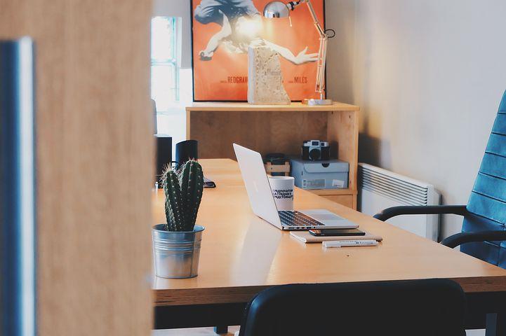Offene Tür zum Büro, ein heller Arbeitsplatz mit Laptop, signalisiert Gesprächbereitschaft