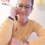 Frau mit Brille am Tisch, Textmarker in rechter Hand, linke Hand liegt auf, lächelt
