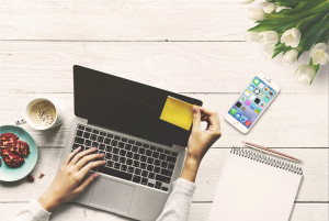 Home of Personalarbeit Blogbanner Schreibtisch mit Laptop, Kaffe, Handy, ein Postit wird an den Bildschirm geklebt