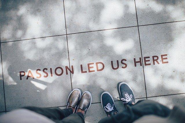 """Perspektive von oben, zwei Leute schauen auf Schriftzug am Boden """"passion led us here"""""""