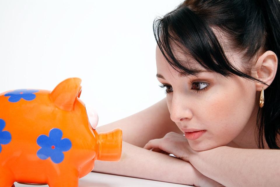Frau lehnt auf Tisch mit verschränkten Armen, starrt auf ein orangenes Sparschwein