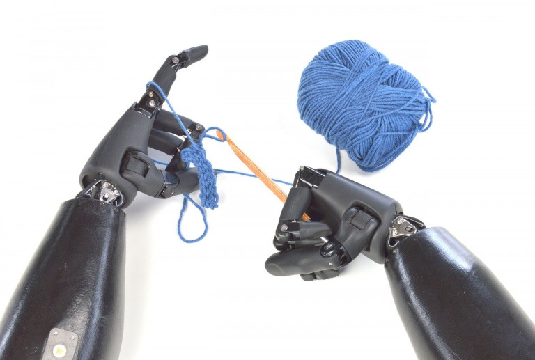 Zwei schwarze Roboterhände stricken blaue Wolle